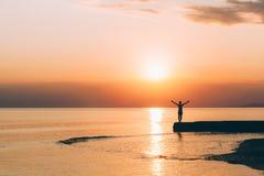 Junge Frau, die mit den angehobenen Armen im Sonnenuntergang steht Lizenzfreies Stockbild