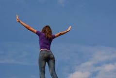 Junge Frau, die mit den angehobenen Händen bleibt Lizenzfreies Stockbild