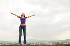 Junge Frau, die mit den angehobenen Händen bleibt Lizenzfreie Stockfotografie