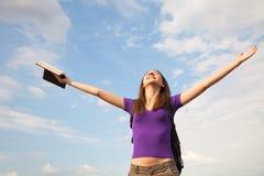 Junge Frau, die mit den angehobenen Händen bleibt Lizenzfreie Stockfotos