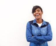 Junge Frau, die mit den Armen gekreuzt lacht Lizenzfreies Stockfoto