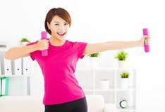 junge Frau, die mit Dummköpfen im Wohnzimmer trainiert Stockfotos