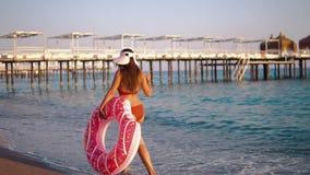 Junge Frau, die mit einem aufblasbaren Donut, Rückseite schwimmt stock video