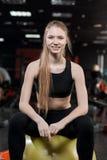 Junge Frau, die mit einem Ball in der Turnhalle sitzt Lizenzfreies Stockfoto