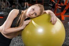 Junge Frau, die mit einem Ball in der Turnhalle sitzt Lizenzfreie Stockfotos