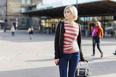 Junge Frau, die mit einem fahrbaren Koffer reist Stockfotografie