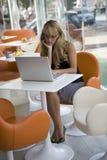 Junge Frau, die mit einem Laptop in einem Kaffee arbeitet Stockfoto