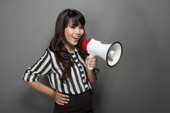 Junge Frau, die mit einem Megaphon gegen grauen Hintergrund schreit Stockfotos