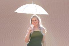 Junge Frau, die mit einem Regenschirm in der Wüste aufwirft Stockbild