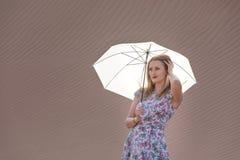 Junge Frau, die mit einem Regenschirm in der Wüste aufwirft Lizenzfreie Stockbilder
