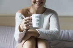Junge Frau, die mit einem Tasse Kaffee lächelt Stockfotos