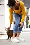 Junge Frau, die mit einer Katze auf Stadtstraße spielt Stockbild