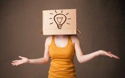 Junge Frau, die mit einer Pappschachtel auf ihrem Kopf mit ligh gestikuliert Lizenzfreies Stockfoto