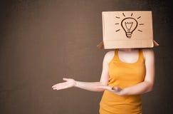 Junge Frau, die mit einer Pappschachtel auf ihrem Kopf mit ligh gestikuliert Stockbilder