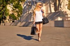 Junge Frau, die mit Einkaufstaschen im Sonnenuntergang geht Stockfotos