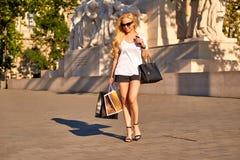 Junge Frau, die mit Einkaufstaschen im Sonnenuntergang geht Lizenzfreie Stockfotografie