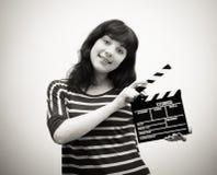 Junge Frau, die mit Filmscharnierventilbrett lächelt stockfotos