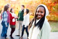 Junge Frau, die mit Freunden im Hintergrund lächelt Stockfoto