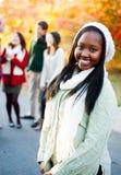 Junge Frau, die mit Freunden im Hintergrund lächelt Stockfotos