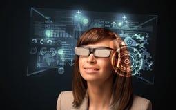 Junge Frau, die mit futuristischen intelligenten High-Techen Gläsern schaut Stockfoto