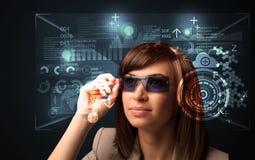 Junge Frau, die mit futuristischen intelligenten High-Techen Gläsern schaut Lizenzfreie Stockbilder