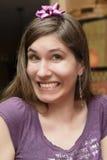 Junge Frau, die mit Geschenkbogen auf ihrem Kopf grinst stockfotos