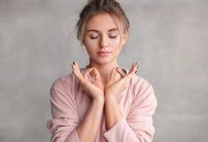Junge Frau, die mit geschlossenen Augen meditiert stockfotos