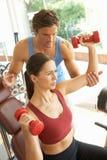 Junge Frau, die mit Gewichten in der Gymnastik arbeitet Stockbild