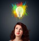Junge Frau, die mit Glühlampe über ihrem Kopf denkt Lizenzfreies Stockbild