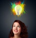Junge Frau, die mit Glühlampe über ihrem Kopf denkt Lizenzfreie Stockbilder