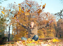 Junge Frau, die mit Herbstblättern spielt lizenzfreies stockfoto