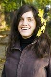 Junge Frau, die mit Herbstblatt lächelt Stockbilder