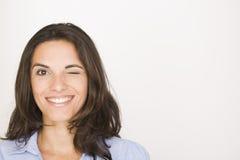 Junge Frau, die mit ihrem Auge blinzelt Lizenzfreie Stockfotos