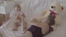Junge Frau, die mit ihrem Baby sitzt, das, spielend mit der Babyflasche, die im Bett sitzt, gebotener Spielzeugbär nah ist recht stock video footage