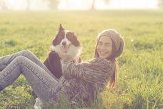 Junge Frau, die mit ihrem border collie-Hund spielt Lizenzfreie Stockbilder