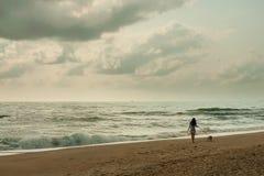 Junge Frau, die mit ihrem Hund auf dem Strand mit schönem Himmel (Retrostil, geht) lizenzfreie stockfotos