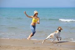 Junge Frau, die mit ihrem Hund spielt Stockbild