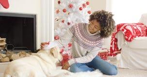 Junge Frau, die mit ihrem Hund am Weihnachten sich entspannt Stockfotografie