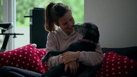 Junge Frau, die mit ihrem schwarzen Hund streichelt und spielt stock footage