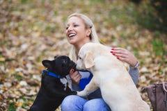 Junge Frau, die mit ihren Hunden spielt lizenzfreies stockfoto