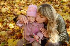 Junge Frau, die mit ihrer kleinen Tochter im autu spielt stockbild