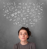 Junge Frau, die mit Ikonen des Sozialen Netzes über ihrem Kopf denkt Lizenzfreie Stockbilder