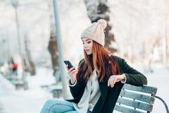 Junge Frau, die mit intelligentem Telefon und Winter lächelt Lizenzfreie Stockbilder