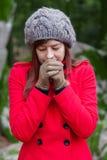Junge Frau, die mit Kälte auf einem Wald zittert Stockfotos