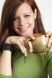 Junge Frau, die mit Kaffee lächelt Lizenzfreie Stockfotos