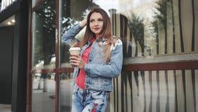 Junge Frau, die mit Kaffee, vor einer Kaffeestube steht outdoor stock footage