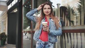 Junge Frau, die mit Kaffee, vor einer Kaffeestube steht outdoor stock video