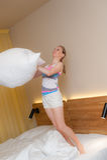 Junge Frau, die mit Kissen spielt Stockfoto