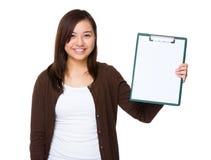 Junge Frau, die mit Klemmbrett darstellt Stockbilder