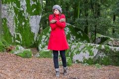 Junge Frau, die mit Kälte auf einem Wald zittert Stockfotografie